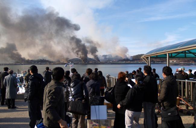大延坪(テヨンピョン)島から上がる砲撃による煙をみつめる人たち.jpg